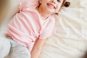 Cute little girl in bedroom jumping on a bed
