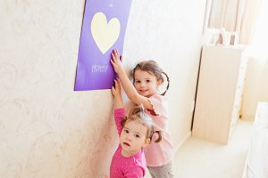 Mothers day, girls holding greeting card for their mum