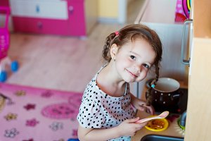 Little girl with braids drawing playing with toy kitchen