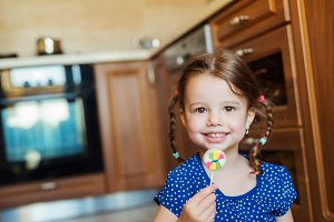 Little girl in the kitchen smiling, eating lollipop