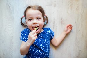 Little girl lying on the floor, smiling, eating lollipop