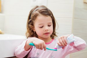 Little girl in bathroom putting a toothpaste on toothbrush