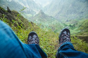 Traveler hiking boots over impressive verdant Xo-Xo valley with mountain peaks, rugged cliffs on Santo Antao Island, Cape Verde