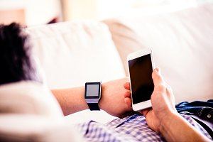 Unrecognizable man at home using smartphone and smart watch