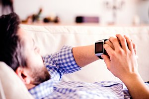 Man lying on sofa at home using smart watch