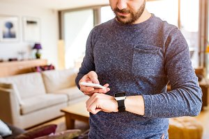 Man working from home using smartphone and smart watch