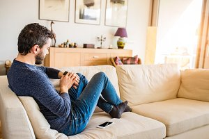 Man at home sitting on sofa using smart watch