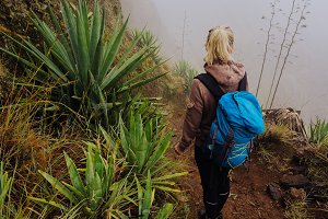 Female traveler staying on the edhe of inactive cove volcano crater above the foggy green valley overgrown with yucca plants. Santo Antao island in Cabo Verde