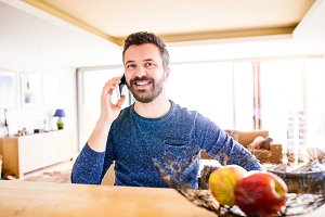 Businessman working from home, holding smartphone making phone c