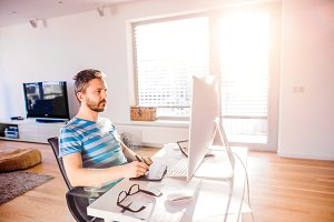 Man sitting at desk working from home on computer