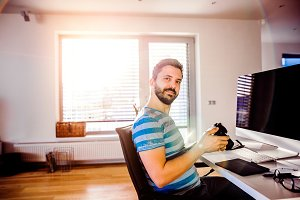 Man sitting at desk working from home holding camera