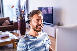 Man working from home on computer, wearing headset