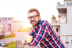 Businessman with cup of coffee standing on balcony, relaxing