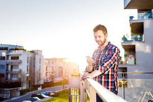 Hipster businessman with smart phone texting, standing on balcon
