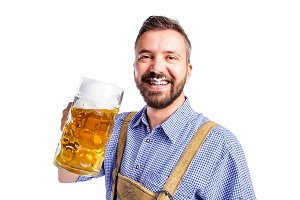 Man in traditional bavarian clothes drinking beer