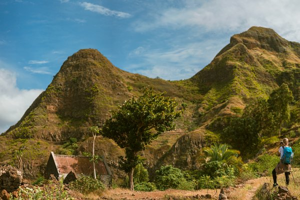 People Stock Photos: Igor Tichonow - Panoramic view of woman tourist with blue backpack making photo of landscape in Mountains of Santo Antao island, Cabo Verde
