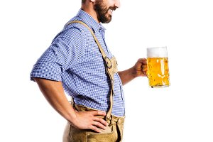 Unrecognizable man in bavarian clothes holding mug of beer