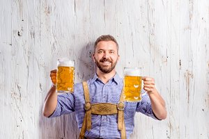 Man in traditional bavarian clothes holding two beers