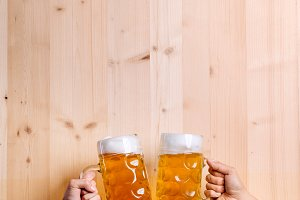 Two unrecognizable men clinking with beer mugs, studio shot