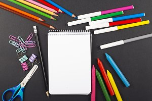 Colored pencils, stationery, and notebook on black background. Back to school concept.