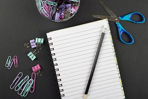 Stationery next to notebook, pencil and scissors on black background. Back to school concept.