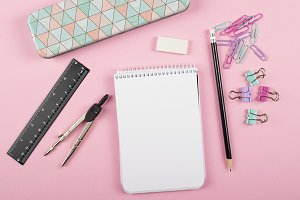 Notebook next to compass, clips, ruler and pencil on pink background. Back to school concept.
