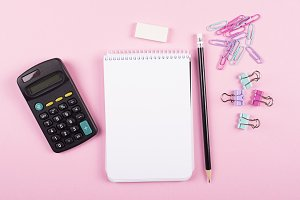 Notebook next to clips calculator, and pencil on pink background. Back to school concept.