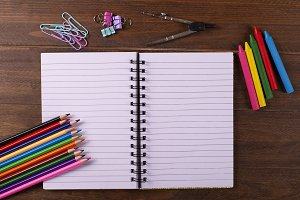 Colored pencils, compass, stationery and notebook on wooden table. Back to school concept.