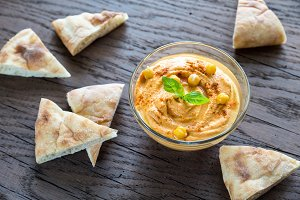 A bowl of hummus with pita