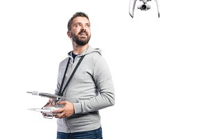 Man with flying drone. Studio shot on white background, isolated