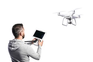 Man with flying drone. Studio shot on white background, isolated.