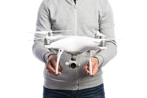 Unrecognizable man holding drone. Studio shot, isolated
