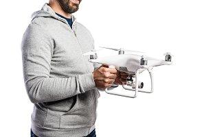 Unrecognizable man holding drone. Studio shot, isolated