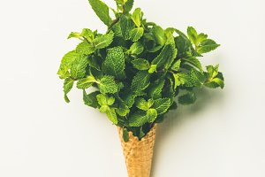 Waffle cone with fresh mint leaves over white background