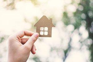 hand holding model house