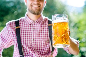 Man in traditional bavarian clothes holding mug of beer