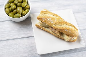 Omelet sandwich with potatoes next to bowl with olives on wooden table. Typical spanish food.