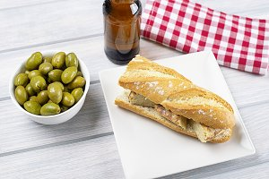 Omelet sandwich with potatoes next to bowl with olives and a beer on wooden table. Typical spanish food.