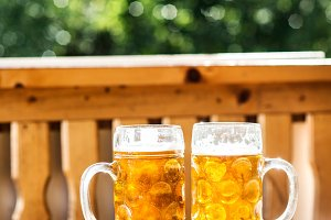Two mugs of beer on wooden table, sunny day