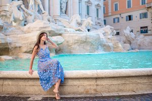 Young beautiful girl near fountain Fontana di Trevi with city map
