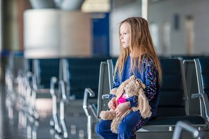 Adorable little girl with baggage in airport waiting for boarding