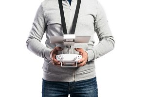 Unrecognizable man with flying drone. Studio shot, isolated.