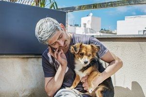 Man with his dog, talking to phone.
