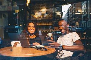 Black man and white woman drinkcoffe