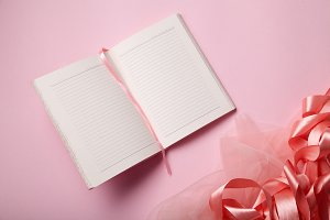 Empty notebook with text space and shiny pink satin ribbon
