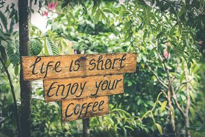 Life is short enjoy your coffee text on a wooden plate in the tropics of Bali island, Indonesia.