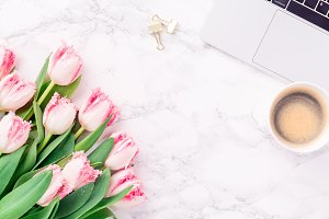 Pink tulips and coffee on the desk