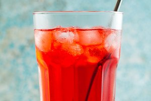 red summer tea with berries in a glass with ice and alcohol. sum