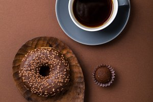 Chocolate donuts on brown background