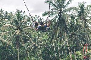Couple swings in the deep jungle of Bali island.
